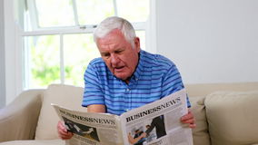 Mature man reading his newspaper. At home stock video footage
