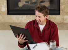 Mature man reading information from his computer while at home Stock Photo