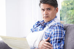 Mature Man Reading Letter About Injury Royalty Free Stock Image