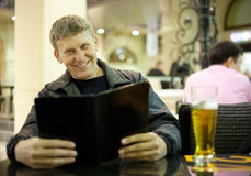 Mature man reading menu card Royalty Free Stock Image