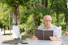 Mature man reading the menu at a restaurant Royalty Free Stock Images