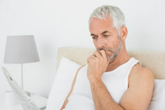 Mature man reading newspaper in bed Royalty Free Stock Photography
