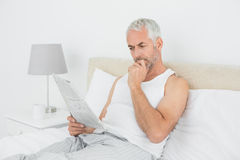 Mature man reading newspaper in bed at home Stock Photos