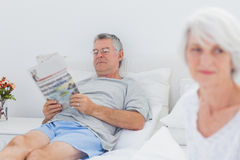 Mature man reading a newspaper in bed Royalty Free Stock Photo