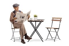 Mature man reading a newspaper at a coffee table stock image