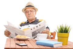 Mature man reading a newspaper seated at a coffee table Royalty Free Stock Images