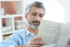 Mature man reading newspaper sitting at home Stock Photography