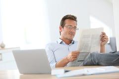 Mature man reading newspaper Royalty Free Stock Image