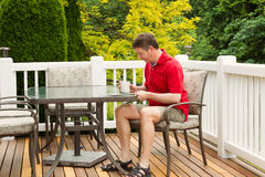 Mature Man reading outside on patio Royalty Free Stock Image