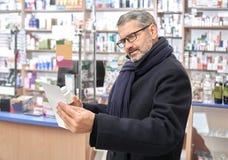Mature man reading prescription in drugstore. stock photos