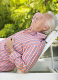 Mature Man Reclining On Lounge Chair. Side view of a mature man reclining on lounge chair outdoors Stock Photos