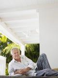 Mature Man Reclining On Verandah Stock Photo