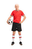 Mature man in a red jersey holding a football Stock Photography