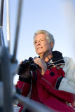 Mature man, in red waterproof jacket, standing on deck of yacht, holding pair of binoculars, smiling, low angle view (differential Stock Photography