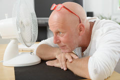 Mature man refreshed with a fan. A mature man refreshed with a fan Royalty Free Stock Image