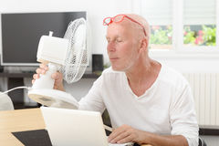Mature man refreshed with a fan. In his home Stock Image