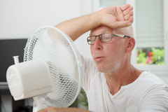 Mature man refreshed with a fan Royalty Free Stock Photography