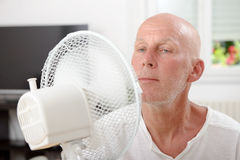 Mature man refreshed with a fan. In his home Royalty Free Stock Photos