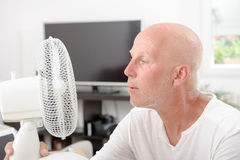 Mature man refreshed with a fan. In his home Royalty Free Stock Photography