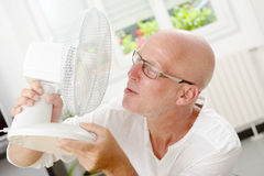Mature man refreshed with a fan. In his home Stock Photography