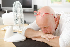 Mature man refreshed with a fan. In his home Royalty Free Stock Photo