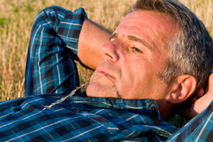 Mature man relax. Mature man with little straw in his mouth thinking and looking away lying on a yellow meadow in summer stock photo