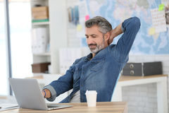 Mature man relaxing drinking coffee in front of laptop Royalty Free Stock Photography