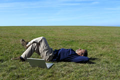 Mature man relaxing in field next to laptop Stock Photography