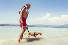 Mature man relaxing with his dog in the fresh water Royalty Free Stock Images