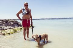 Mature man relaxing with his dog in the fresh water Royalty Free Stock Photography