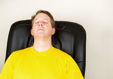 Mature Man Relaxing in Massage Chair. Horizontal photo of mature man relaxing in massage chair with eyes closed stock photography