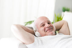 Mature man relaxing with music on the sofa. Mature man with his hands behind the head sleeping or relaxing while listening to music on the headphones liying on a Stock Photography
