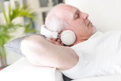 Mature man relaxing with music on the sofa. Mature man with his hands behind the head sleeping or relaxing while listening to music on the headphones liying on a Royalty Free Stock Photos