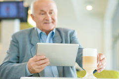 Mature man relaxing and resting at the cafeteria. Relaxing time. Shot of mature concentrated man with laptop, taking coffee mug at the cafeteria Royalty Free Stock Image