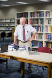 Mature man researching books in library. Mature man standing with textbooks in library, professor doing research Royalty Free Stock Photo