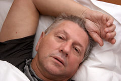 Mature man resting in bed Stock Photo