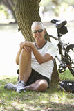 Mature Man Resting On Cycle Ride Through Park Stock Images