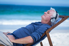 Mature man resting on a deck chair listening to music Royalty Free Stock Image
