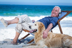 Mature man resting on a deck chair listening to music petting his dog Stock Images