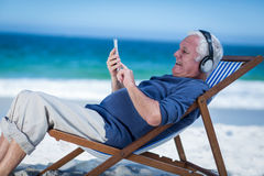 Mature man resting on a deck chair listening to music with smartphone Royalty Free Stock Photo