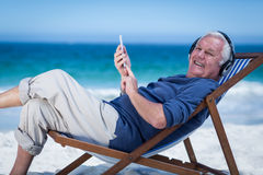 Mature man resting on a deck chair listening to music with smartphone Royalty Free Stock Image