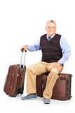 A mature man resting seated on a travel bag Stock Photography