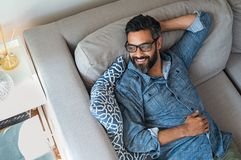 Mixed race man relaxing on couch stock photography