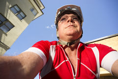 Mature Man Rides Bicycle Downtown Seen from Low Angle Stock Photography