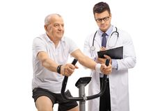 Mature man riding an exercise bike and a doctor writing in a cli Royalty Free Stock Photography