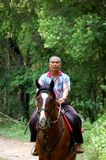Mature man riding horse. Mature Asian man riding horse in countryside with forest in the background Stock Photo