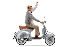 Mature man riding an old-fashioned scooter and holding his hand stock photos