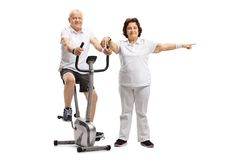 Mature man riding a stationary bike with a mature woman pointing Stock Photos
