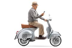 Mature man riding a vintage scooter and looking at his phone royalty free stock photography