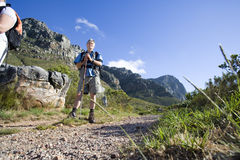 Mature man, with rucksack and hiking pole, standing on mountain trail (surface level) stock photo